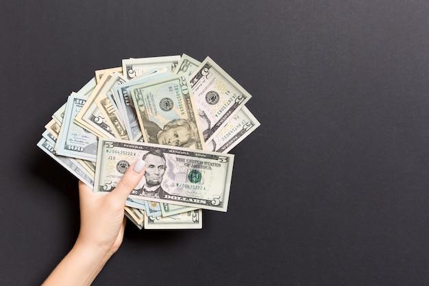 Draufsicht der weiblichen hand verschiedene dollar auf buntem hintergrund halten. darlehenskonzept. wohlstandskonzept