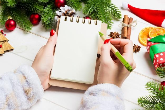 Draufsicht der weiblichen handschrift in einem notizbuch auf hölzernem weihnachten.