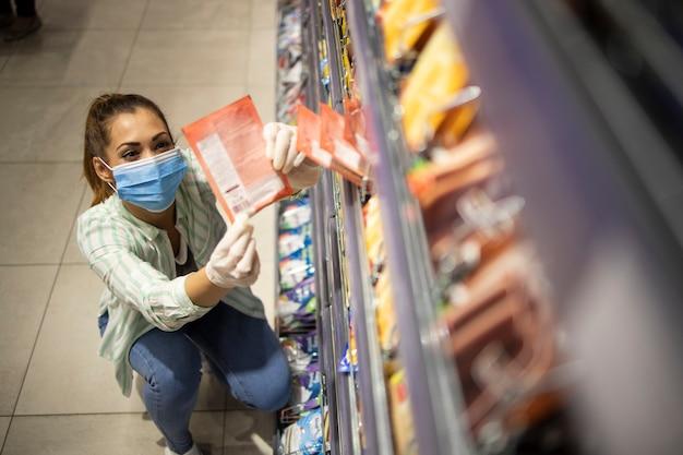 Draufsicht der weiblichen person mit maske und handschuhen, die lebensmittel im supermarkt kaufen