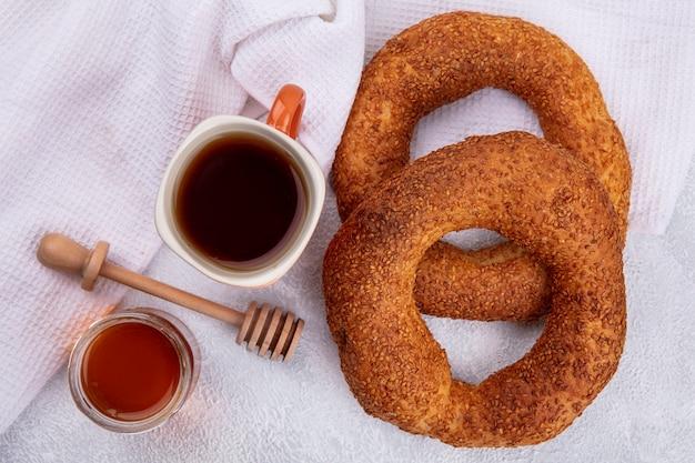 Draufsicht der weichen traditionellen türkischen bagels mit einer tasse tee und honig auf einem glasglas auf einem weißen hintergrund