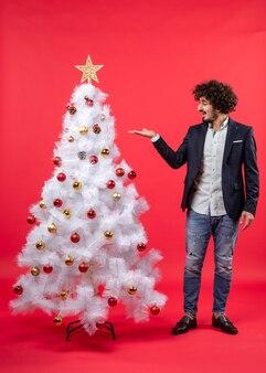 Draufsicht der weihnachtsfeier mit bärtigem jungem mann, der weihnachtsbaum auf rot zeigt