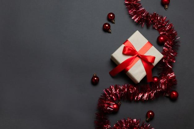Draufsicht der weihnachtsfeiertagsfeier-rotgeschenkbox, zuckerstange, uhr auf rotem hintergrund. vorlage grußkarte.