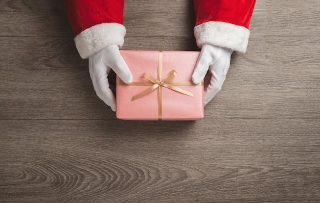 Draufsicht der weihnachtsmannhände hält eine rosa geschenkbox mit goldband auf holz.