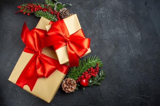 Draufsicht der weihnachtsstimmung mit schönen geschenken mit bogenförmigem band und tannenzweigdekorationszubehör auf der rechten seite auf einem dunklen hintergrund