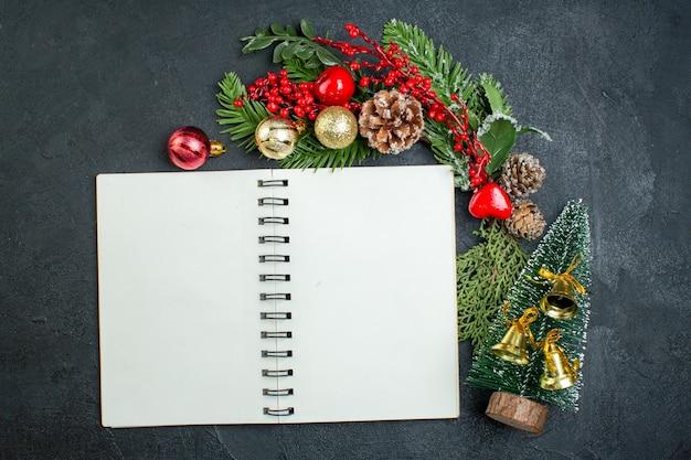 Draufsicht der weihnachtsstimmung mit tannenzweigen-weihnachtsbaum neben spiralblock auf dunklem hintergrund