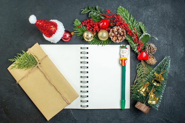Draufsicht der weihnachtsstimmung mit tannenzweigen weihnachtsmannhut-weihnachtsbaum-geschenkbox auf notizbuch auf dunklem hintergrund