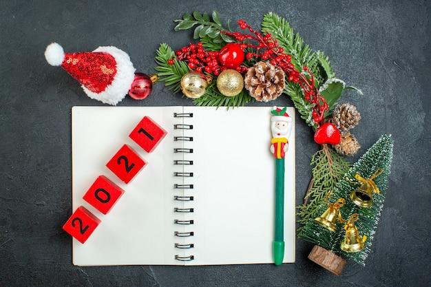 Draufsicht der weihnachtsstimmung mit tannenzweigen weihnachtsmannhut-weihnachtsbaumnummern auf notizbuch auf dunklem hintergrund