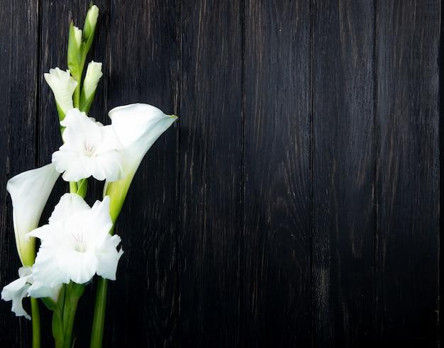 Draufsicht der weißen farbe gladiolen- und callalilienblumen lokalisiert auf schwarzem hintergrund mit kopienraum