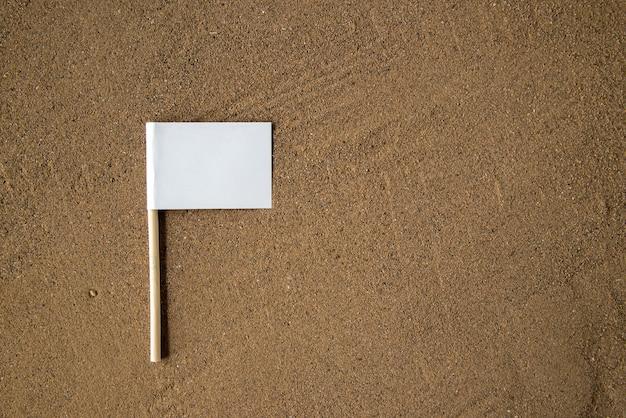 Draufsicht der weißen flagge auf braunem sand