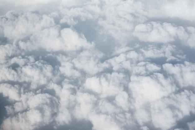 Draufsicht der weißen flaumigen wolken vom flugzeugfenster.