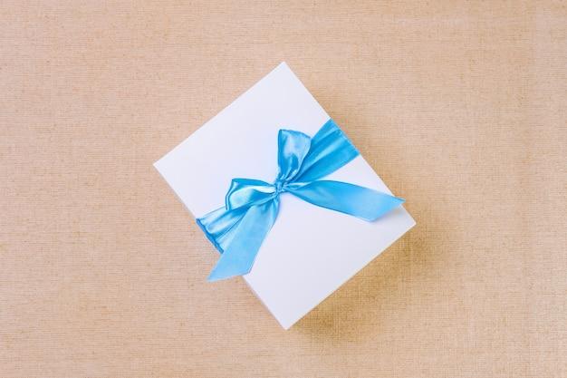 Draufsicht der weißen geschenkbox gebunden durch blaues band