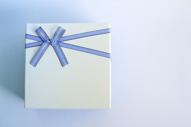 Draufsicht der weißen geschenkbox oder der geschenkboxverpackung mit einem blauen band und einer schleife