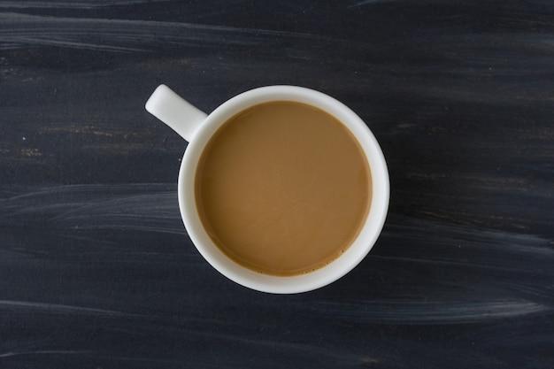 Draufsicht der weißen kaffeetasse über schwarze tabelle