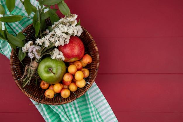 Draufsicht der weißen kirsche mit farbigen äpfeln und blumen in einem korb auf einer roten oberfläche