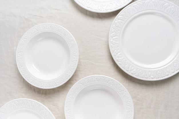 Draufsicht der weißen leeren keramischen platten auf leinentischdecke mit kopienraum. vorbereitung auf das gedeck. konzept food table serving.