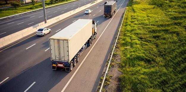 Draufsicht der weißen lkw-bewegungsunschärfe auf autobahnstraße mit container, transportkonzept.