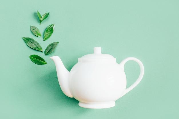 Draufsicht der weißen teekanne und der teeblätter auf grüner oberfläche