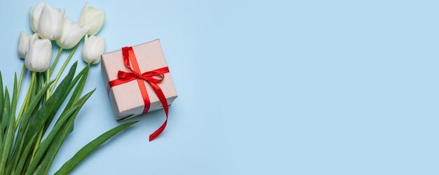 Draufsicht der weißen tulpe blüht blumenstrauß, geschenkbox mit bürokratie auf blauem hintergrund