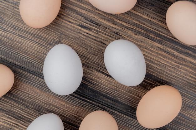 Draufsicht der weißen und cremefarbenen hühnereier lokalisiert auf einem hölzernen hintergrund