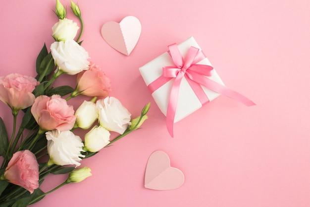 Draufsicht der weißen und rosa blumen der geschenkbox auf dem rosa hintergrund