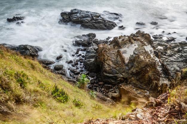 Draufsicht der welle, die die felsen- oder steinküste mit smaragdklarem klarem wasser zusammenstößt