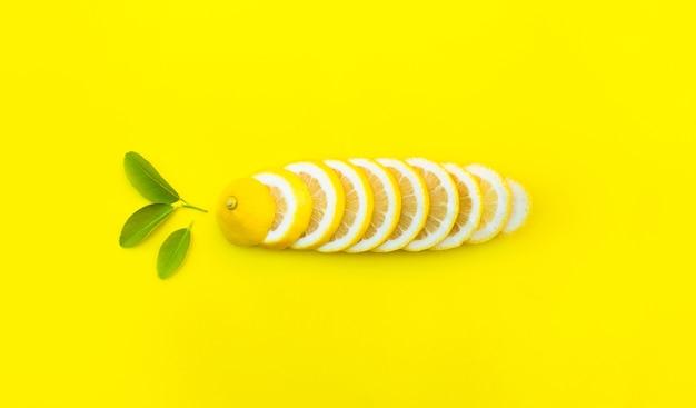 Draufsicht der zitrone und der blätter auf gelbem farbhintergrund