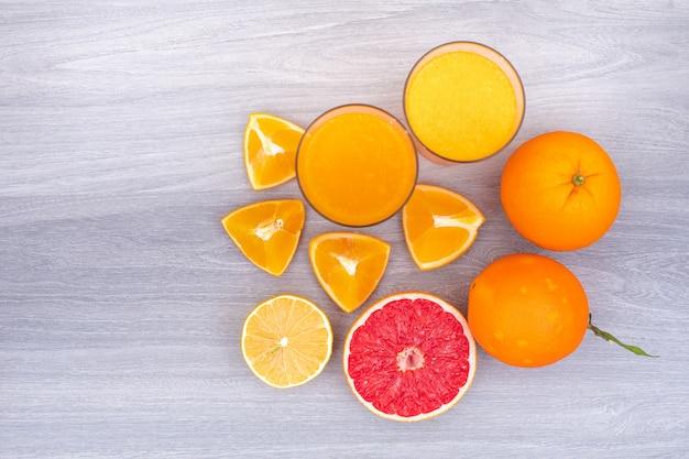 Draufsicht der zitrone und des orangensaftes über weißen holztisch