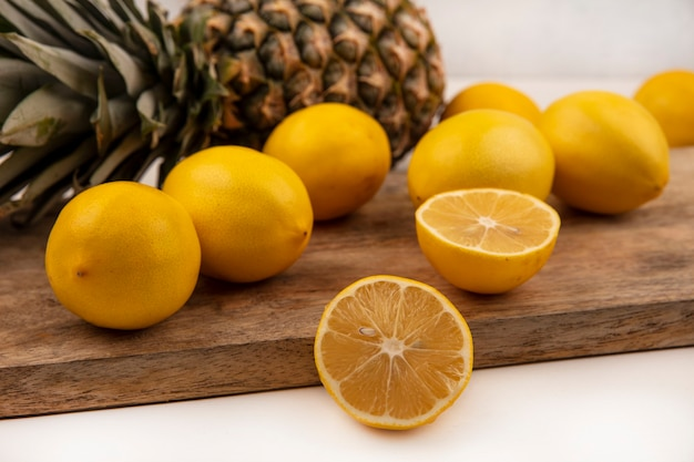 Draufsicht der zitronen der abgerundeten form mit ananas lokalisiert auf einem hölzernen küchenbrett auf einer weißen wand