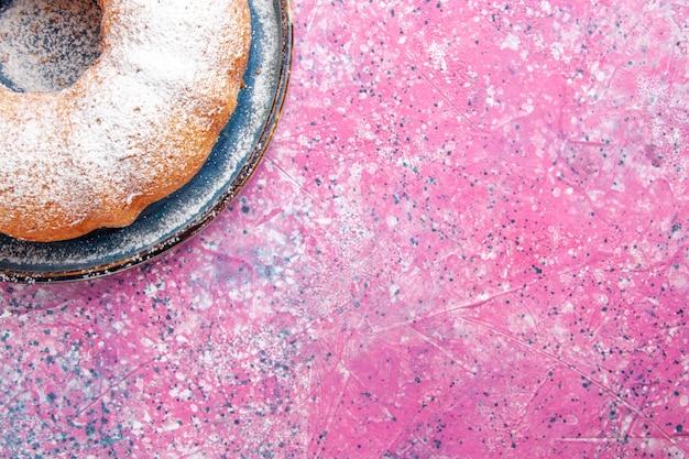 Draufsicht der zuckerpulver-kuchenrunde, die auf rosa-heller oberfläche gebildet wird