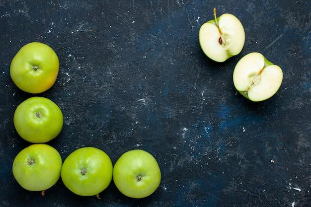 Draufsicht der zusammensetzung der frischen grünen äpfel mit geschnittenem auf dunklem schreibtisch ausgekleidetem, frischem, weichem, reifem obst