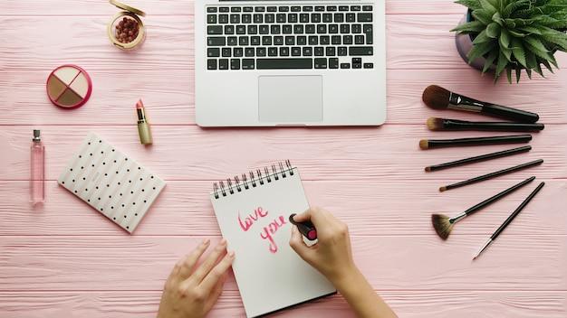 Draufsicht der zusammensetzung mit kosmetika, make-up-werkzeugen, zubehör und frauenhänden, die auf notizbuch auf farboberfläche schreiben. schönheits- und modekonzept.