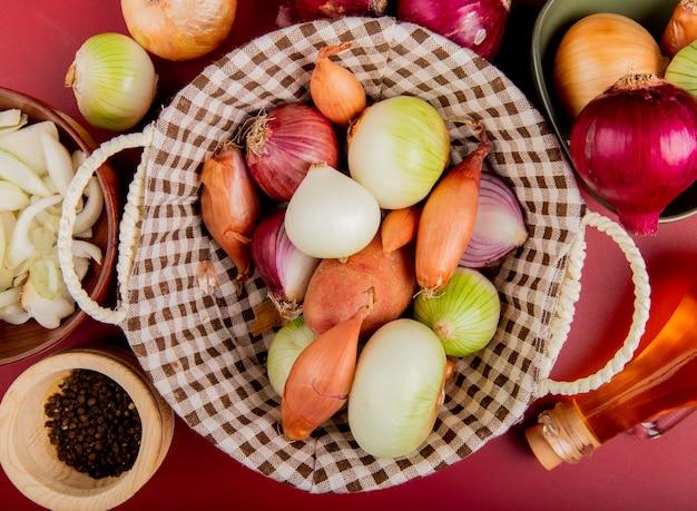 Draufsicht der zwiebeln im korb mit geschnittenem in der schüssel, butter, schwarzen pfeffersamen auf roter oberfläche