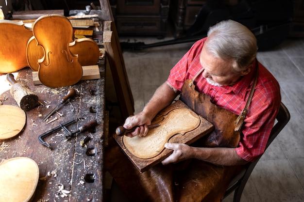 Draufsicht des älteren zimmermanns, der in seiner altmodischen werkstatt arbeitet