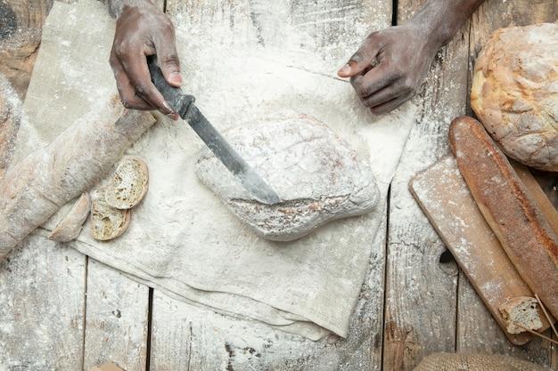 Draufsicht des afroamerikanischen mannes kocht frisches müsli, brot, kleie auf holztisch. leckeres essen, ernährung, bastelprodukt. glutenfreie lebensmittel, gesunde lebensweise, biologische und sichere herstellung. handgemacht.