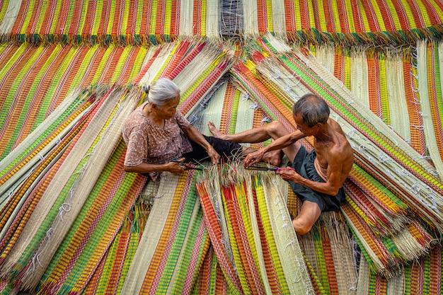 Draufsicht des alten vietnamesischen liebhaberhandwerkers, der die traditionellen vietnam-matten mit glückaktion macht
