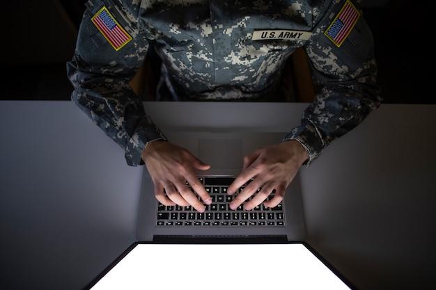 Draufsicht des amerikanischen soldaten in der militäruniform, die auf dem computer tippt
