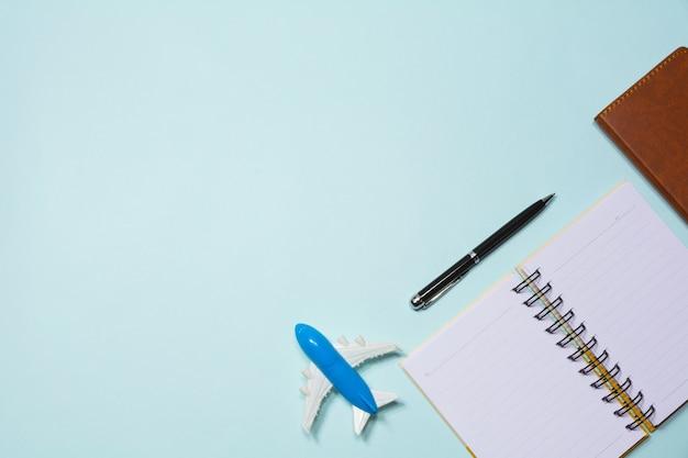 Draufsicht des anmerkungsbuches mit flugzeugspielzeug und -stift auf himmelblauhintergrund mit kopienraum