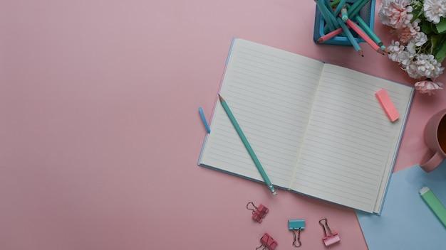 Draufsicht des arbeitsbereichs der weiblichen blogschreiberin mit notizbuch, briefpapier, stiften und kopierraum