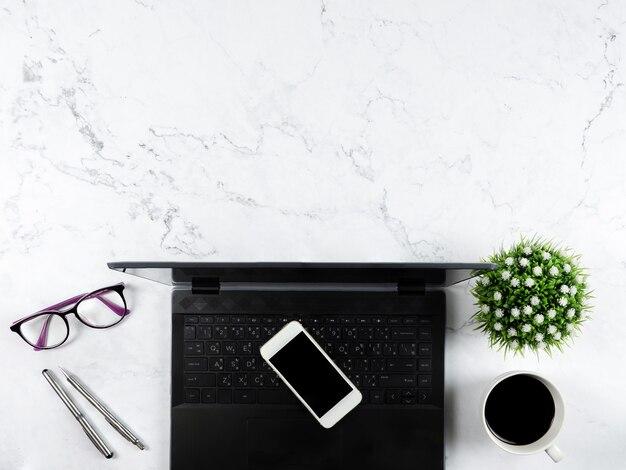 Draufsicht des arbeitsbereichs, laptop-handy-kaffeetasse und gläser auf tischkopierraum