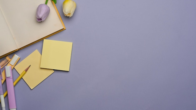 Draufsicht des arbeitsbereichs mit briefpapier, buch, blume und kopienraum auf lila hintergrund