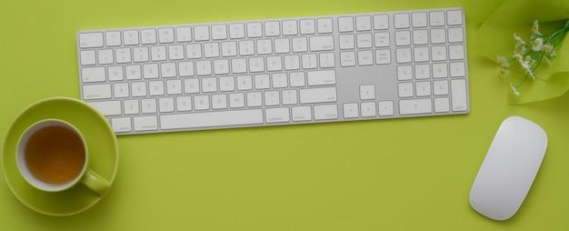Draufsicht des arbeitsbereichs mit computergeräten, teetasse und dekoration auf grünem tisch