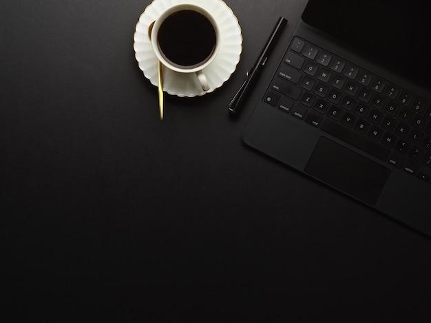 Draufsicht des arbeitsbereichs mit digitalem tablett, kaffeetasse und kopienraum auf schwarzem tisch im arbeitszimmer zu hause