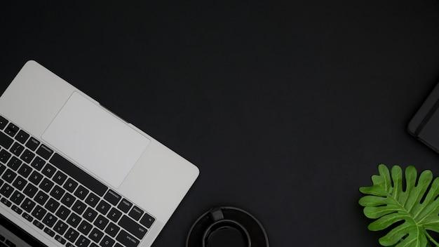 Draufsicht des arbeitsbereichs mit kopierraum, laptop-tastatur und telefon auf schwarzem tisch