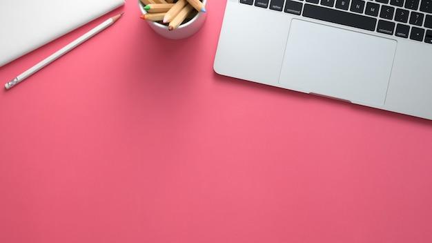 Draufsicht des arbeitsbereichs mit laptop, briefpapier und kopierraum auf rosa tisch