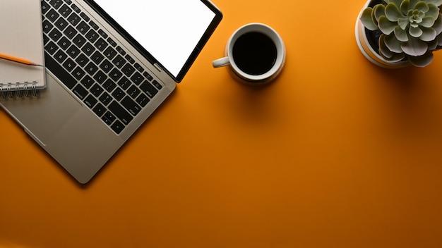 Draufsicht des arbeitsbereichs mit laptop-kaffeetasse-blumentopf und kopierraum im heimbüro