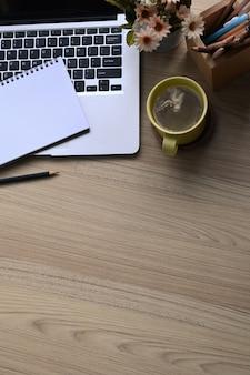 Draufsicht des arbeitsbereichs mit laptop, leerem notizbuch, kaffeetasse