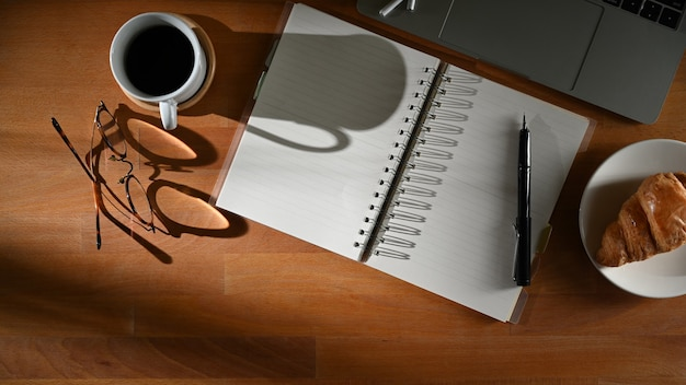 Draufsicht des arbeitsbereichs mit leerem notizbuch, stift, brille, laptop, kaffeetasse und snack auf dem tisch
