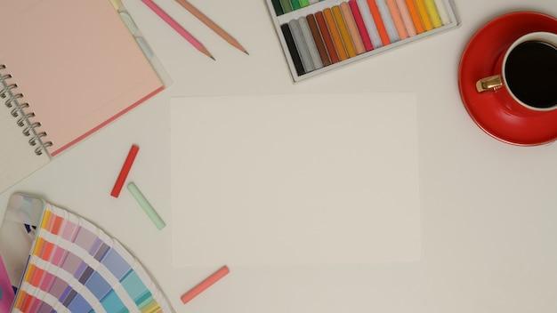 Draufsicht des arbeitsbereichs mit leerem papier, briefpapier, malwerkzeugen und kaffeetasse auf weißem tisch