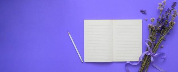Draufsicht des arbeitsbereichs mit offenem notizbuch, bleistift, blumen und kopienraum auf lila tisch