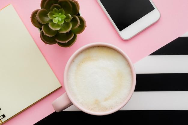 Draufsicht des arbeitsbereichs mit smartphone, tasse kaffee und kopierraum auf rosa wand